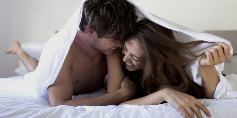 Couple has fun under blanket