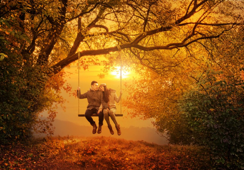 Loving couple swinging in autumn park